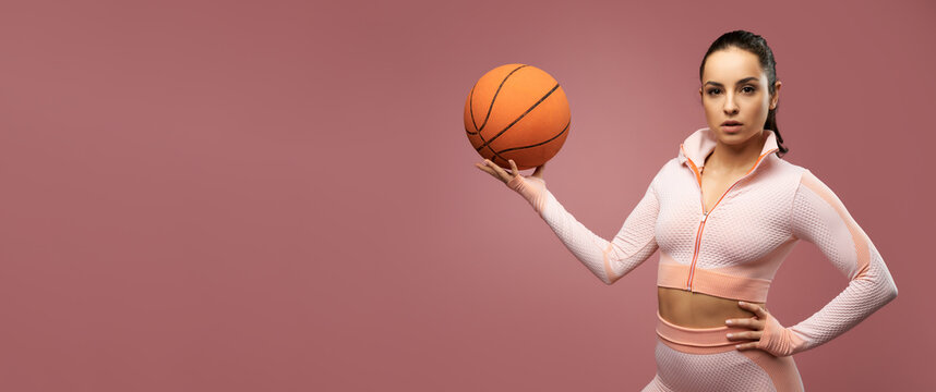 Website header of Sporty young woman with basketball ball posing in studio