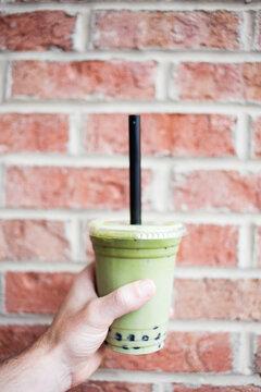 Hand holding a green matcha boba bubble tea