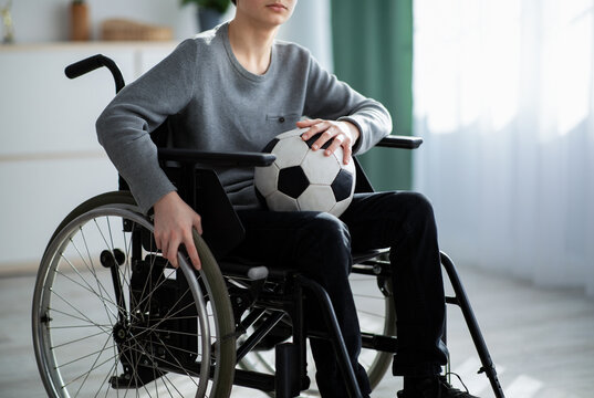 Cropped view of handicapped teen boy with soccer ball sitting in wheelchair, feeling upset over his injury at home