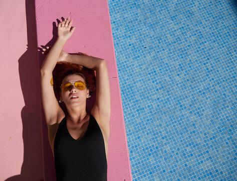 Girl sunbathing on pink border of swimming pool.