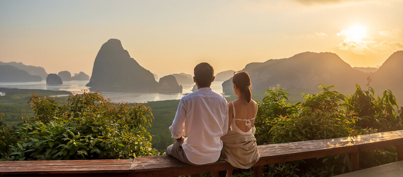Happy couple traveler enjoy Phang Nga bay view point, Tourists relaxing at Samet Nang She, near Phuket in Southern Thailand. Southeast Asia travel, trip, love, together and summer vacation concept
