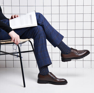 A man in handmade Italian leather shoes sits on a chair and reads a magazine
