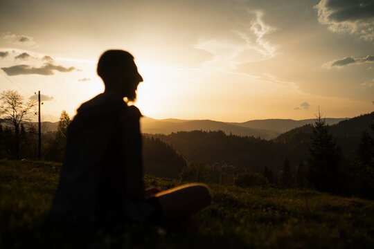 Man sitting at the dramatic sunset in the mountains
