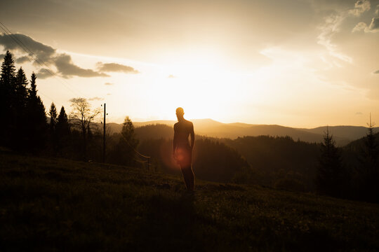 Man walking at the dramatic sunset in the mountains