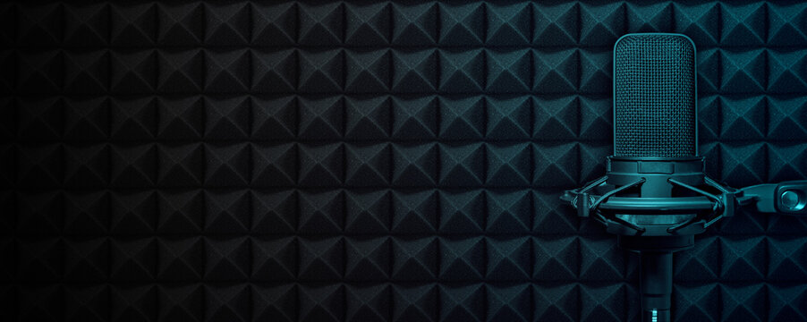 Recording studio microphone on black acoustic foam background with blue light and copy space