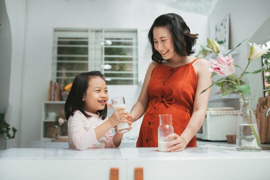 Little asian girl and her pregnant mom drinking milk together at home