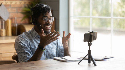 Obraz Enthusiastic african guy vlogger sit at kitchen table talk on cell camera shoot review training tutorial. Active millennial black man teacher record video lesson at home for pupils on distant learning - fototapety do salonu