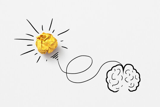 Sketch of human brain with lighting paper bulb.