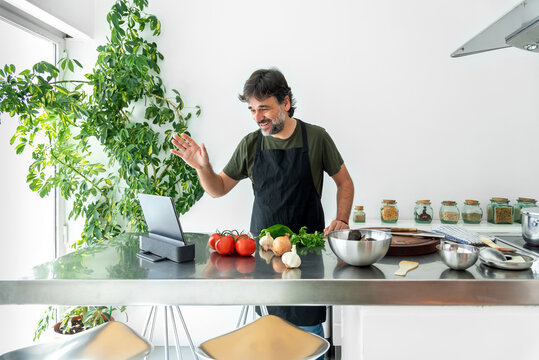 Man making a video conference from his home kitchen