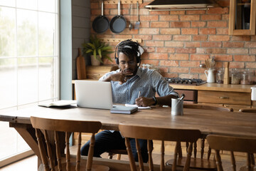 Online education. Young black guy learn foreign language from home using modern tech devices laptop headset. Busy afro male student take notes of virtual lesson prepare written task on teacher demand