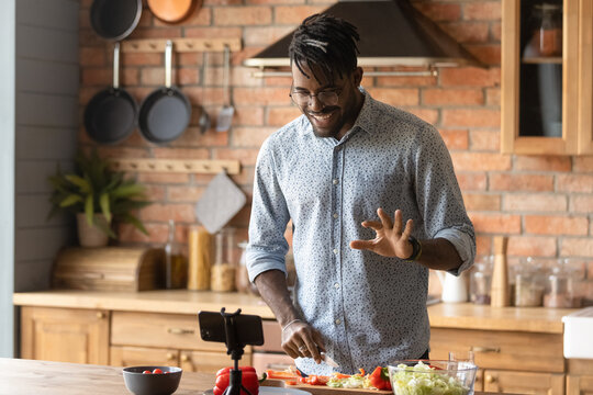 Cooking master class. Confident black man vlogger shoot tutorial teach audience to make healthy food. Young african guy capable cook broadcast live preparing national cuisine dish on domestic kitchen