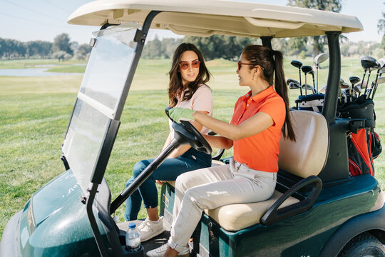 Young women in golf buggy on path