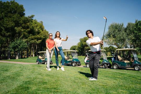 Man playing golf near women