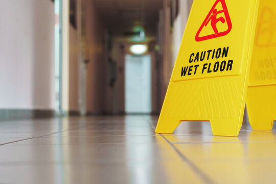 Yellow sign of slippery floor in the room after cleaning