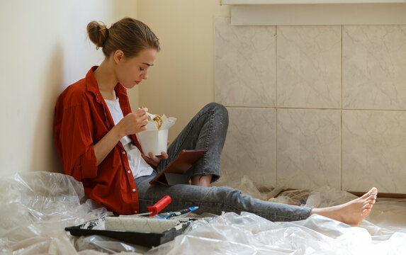 Woman having lunch in messy room