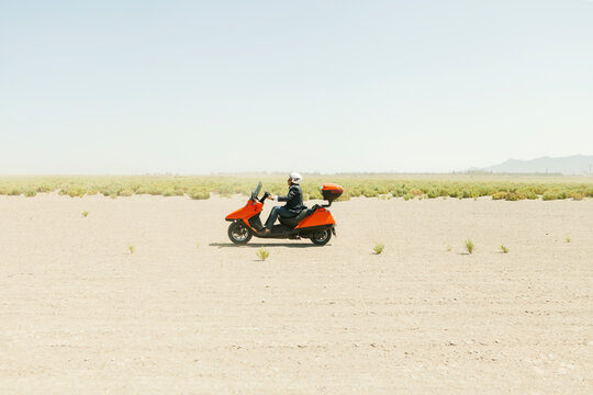 Man Driving a scooter in the desert