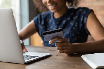 Fototapeta Close up of happy smiling young african female shopper hold credit card pay online safe fast easy. Satisfied black woman loyal client of electronic bank service make transaction using laptop web app obraz