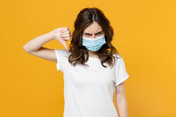 Young woman in white basic blank print design t-shirt in sterile face mask from coronavirus virus...