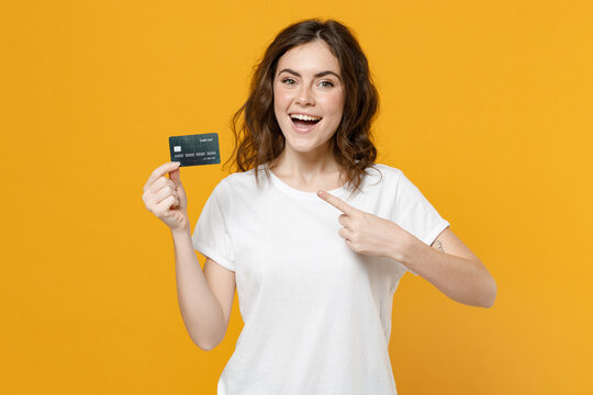 Young surprised happy rich caucasian student woman 20s wearing white basic t-shirt pointing index finger on credit bank card looking camera isolated on yellow orange color background studio portrait.