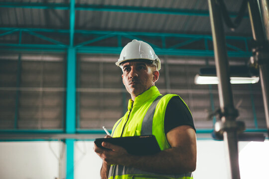Portrait of engineer foreman writing on digital tablet and checking in industrial factory. worker in safety uniform working at construction site. heavy machine technology industry concept. copy space