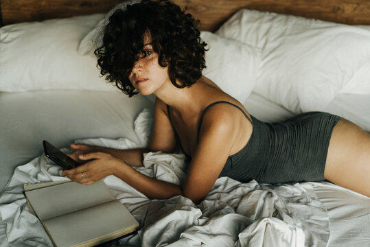Beautiful curly girl in bed with a smartphone