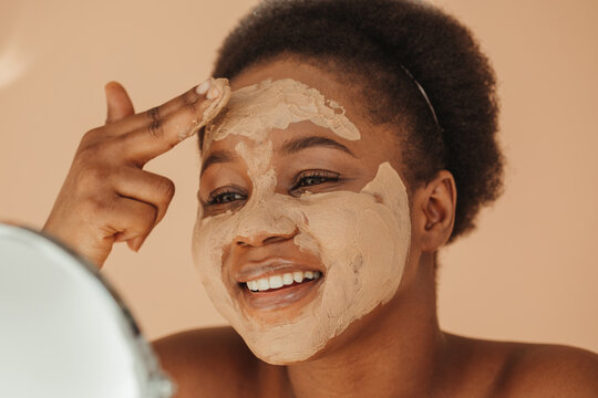 Pretty African American woman applying skincare mask