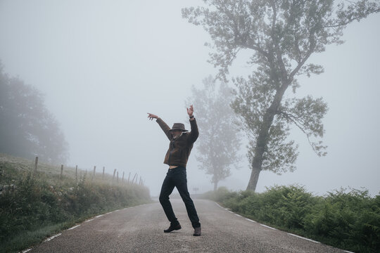 a tall man dances on an empty road in the fog
