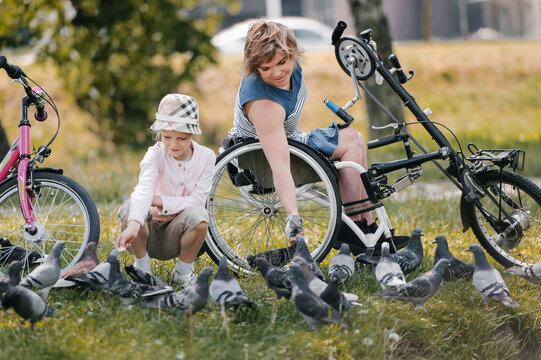 Mother with disability and daughter feeding pigeons