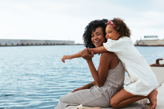 Content woman and teenage girl hugging on waterfront