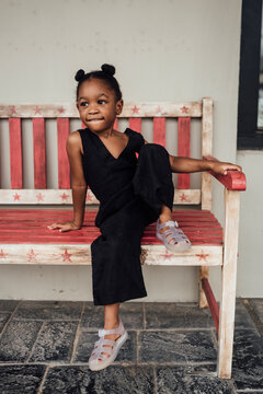 Little girl sitting on a bench enjoying the outdoors
