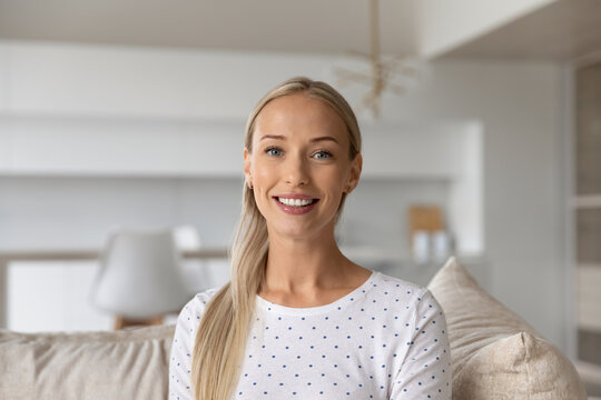 Headshot portrait of smiling young Caucasian woman look at camera talk on video call on gadget. Profile picture screen view of happy female have webcam digital conversation. Virtual event concept.