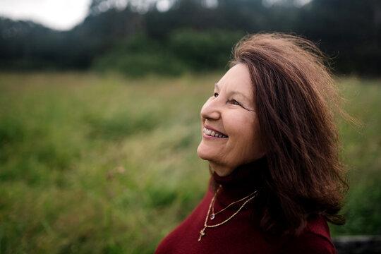 Portrait of older, warm, happy woman outside sitting on fence.