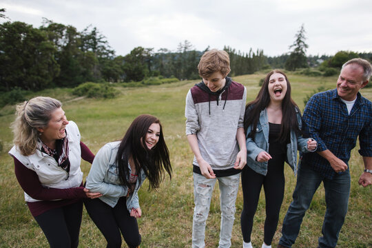 Laughing parents and teenagers together in field