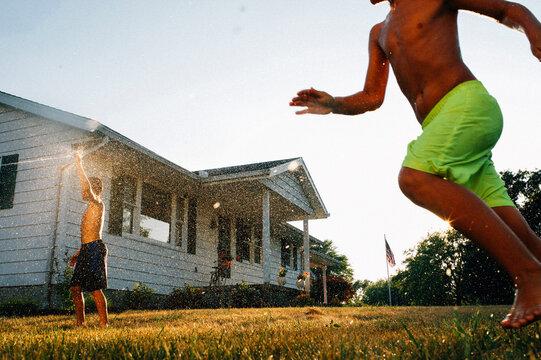 Kids running playing in sprinkler.