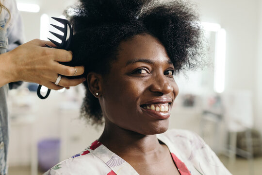 Hairdresser combing hair of black model