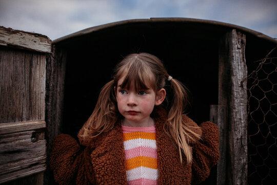 girl standing in the chicken coop doorway