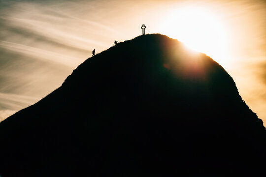 Silhouette Of Two People Pitching Tent On Mountain Peak