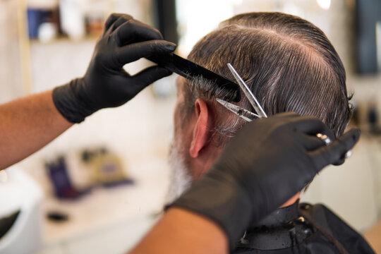 Hairstylist cutting man's hair