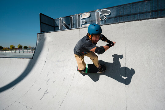 Front view of mid aged man skateboarder in his forties performing stunt on ramp at skate park with safety helmet
