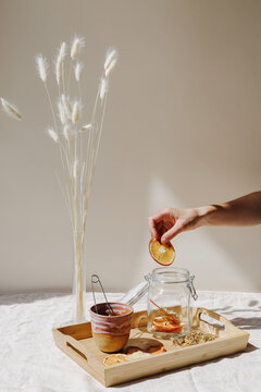 Unrecognizable person brewing tea with dried fruits