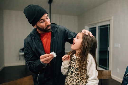 Dad pulling daughter's loose tooth.