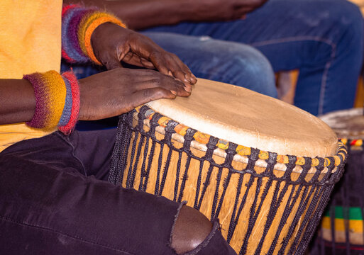 Close up of an African djembe drummer. Drummer playing African percussion music. Ethnic percussion musical instrument Djembe and male hands. Rhythm of Africa.