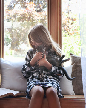 Child Holding Cute Kitten by Window at Home