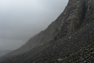 rocky rock with moraine in cloudy and foggy weather