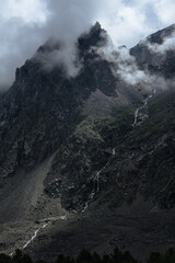 view of a beautiful mountain waterfall falling from a huge black rock