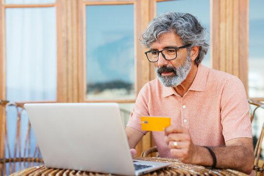Senior man shopping online in an apartment terrace