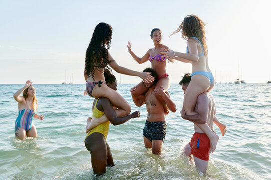 Friends laughing and play fighting in the ocean