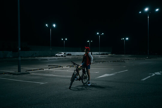 Young woman on bicycle at the parking lot