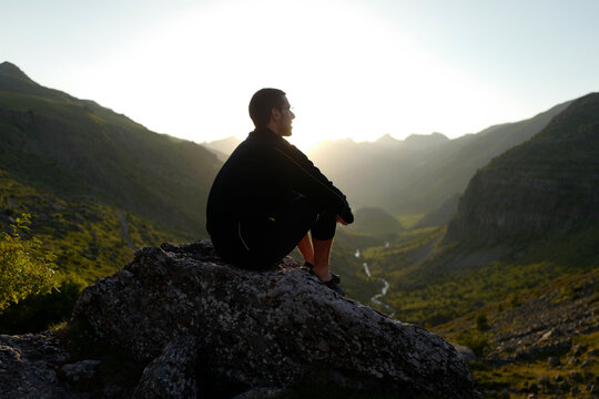 Hiker standing on a rock and looking the sunset over mountains