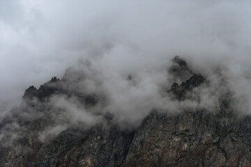 rocky peak, the top of which is covered with clouds